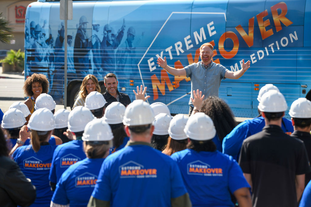 Host Jesse Tyler Ferguson, with designers Breegan Jane, Carrie Locklyn, and Darren Keefe, enthusiastically welcomes a crowd of volunteers in front of the Extreme Makeover Home Edition bus in Hawthorne, California